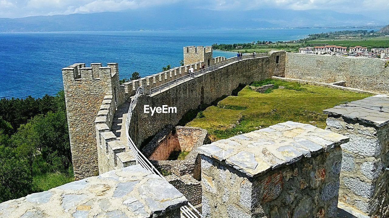 architecture, built structure, history, day, high angle view, outdoors, ancient, nature, castle, no people, old ruin, sky, water, travel destinations, building exterior, sea, horizon over water, scenics, tree, beauty in nature, ancient civilization