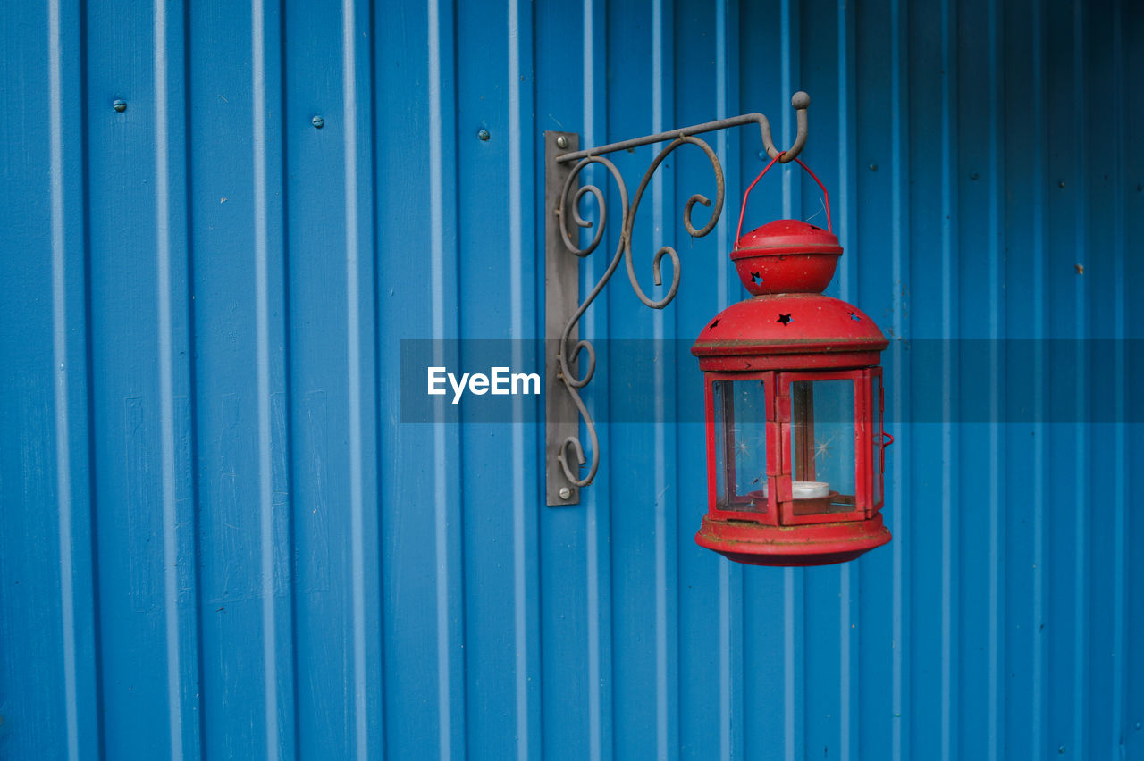 Old Red Lantern Hanging From Metal Mounted On Textured Wall