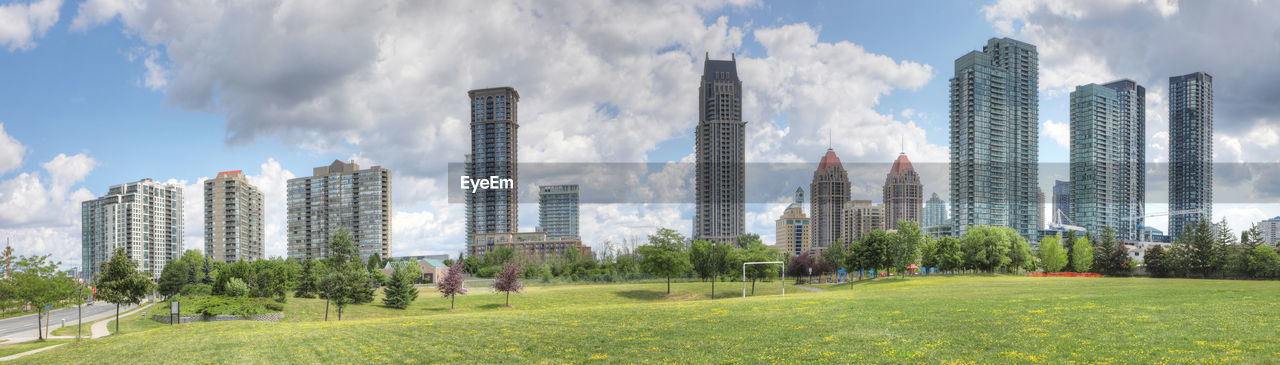 architecture, built structure, building exterior, building, sky, office building exterior, city, cloud - sky, skyscraper, modern, plant, grass, landscape, tall - high, nature, urban skyline, day, residential district, outdoors, green color, no people, cityscape, financial district
