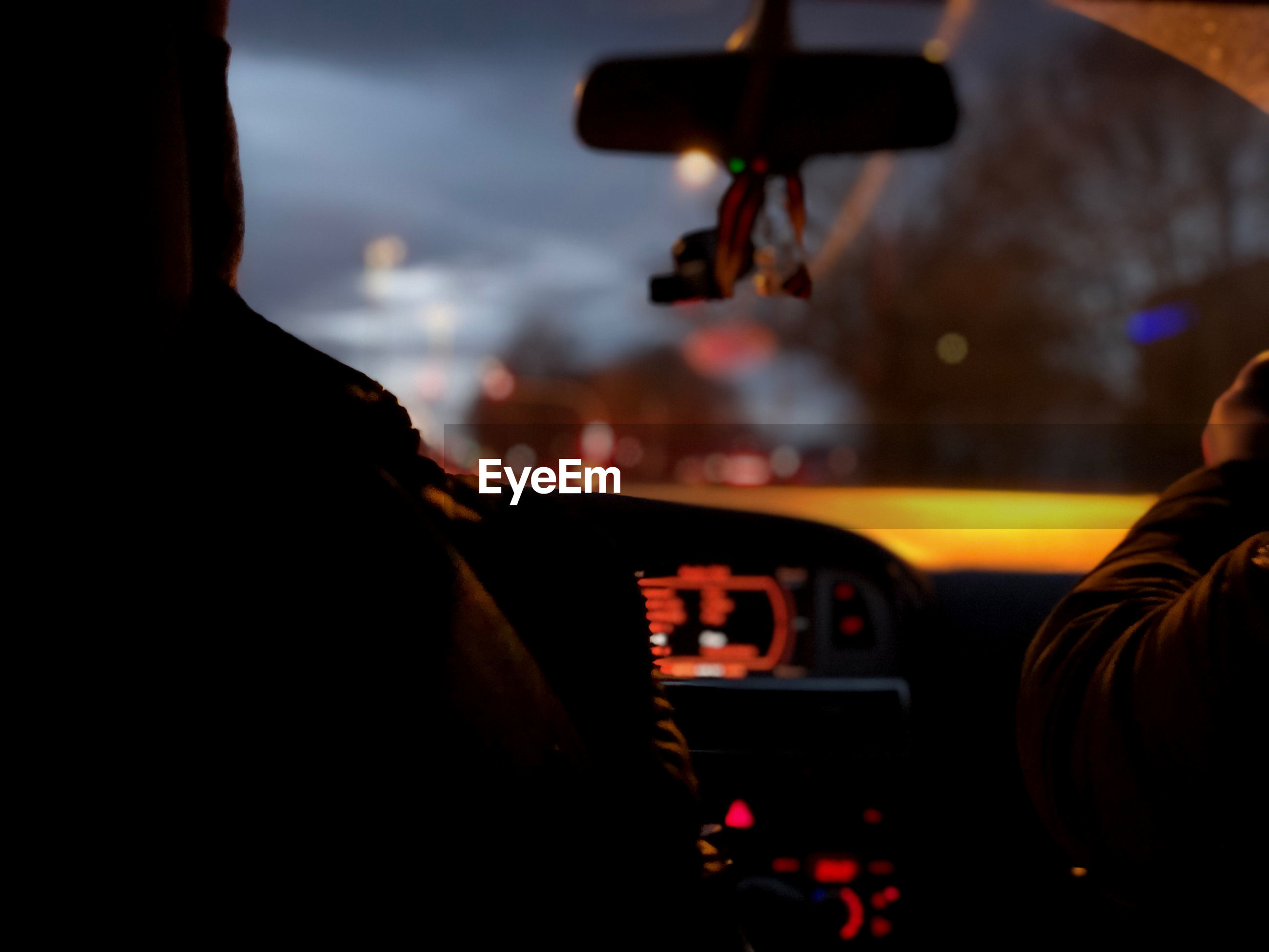 Rear view of people sitting in car at night