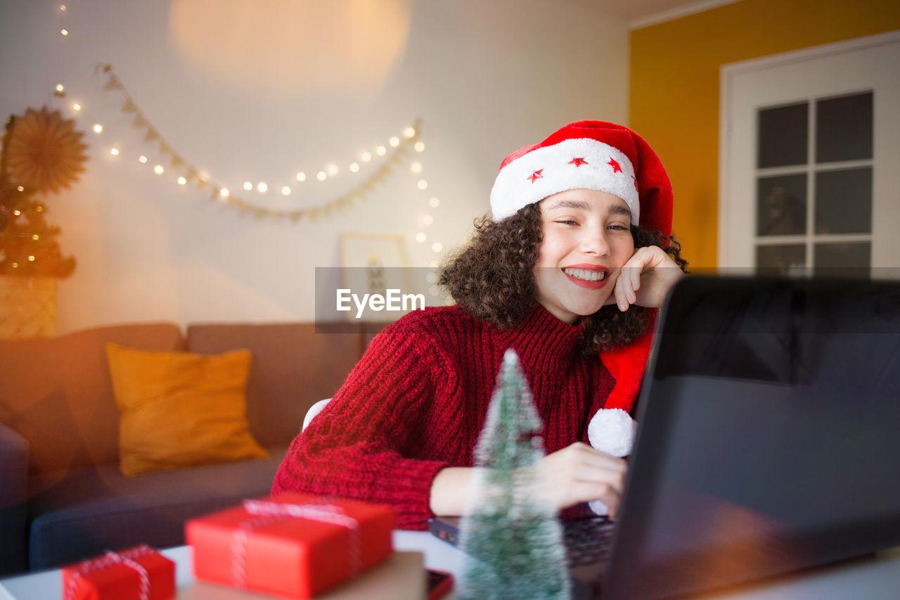 Smiling girl wearing santa hat using laptop at home