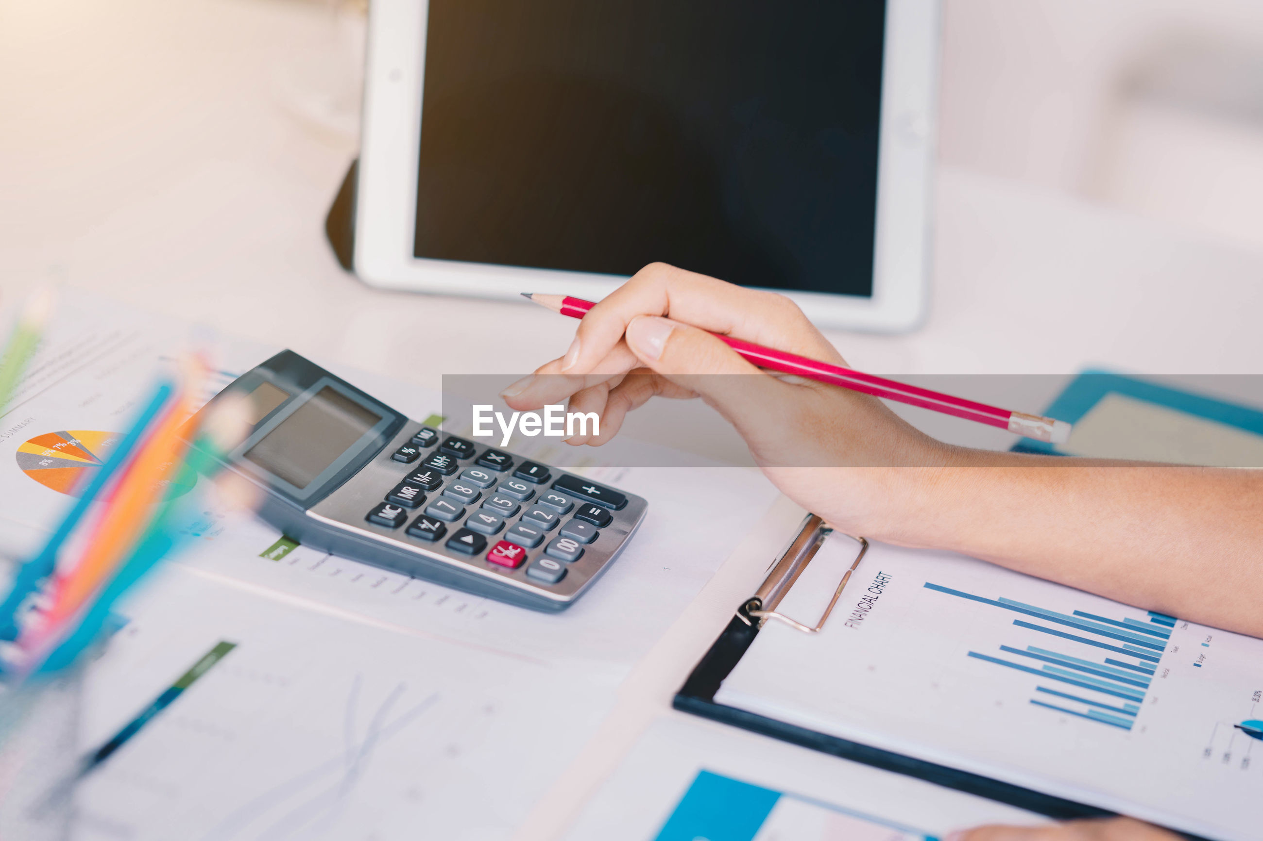 Cropped hand using calculator at table in office