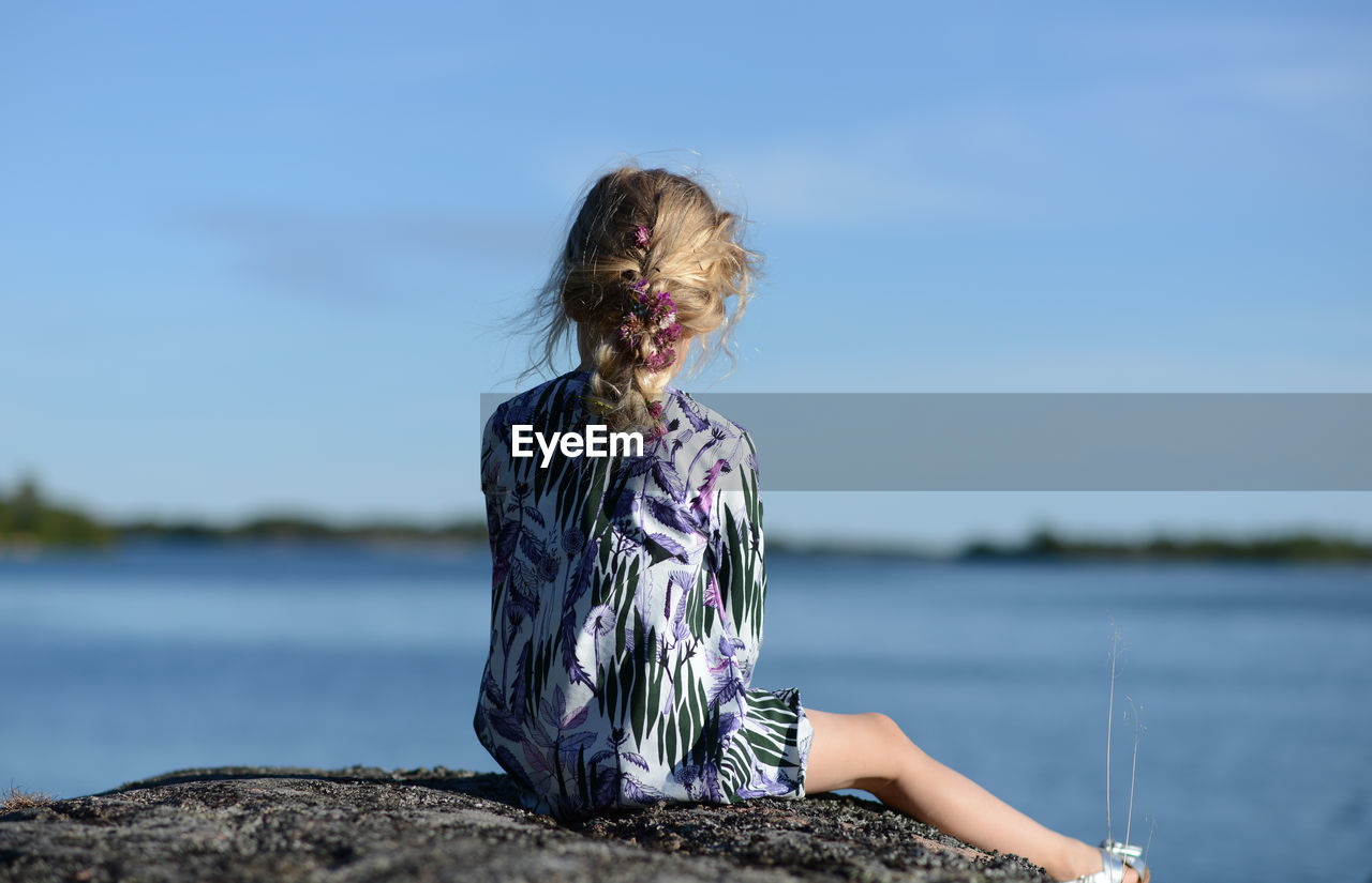 Rear view of girl sitting on rock by sea against sky