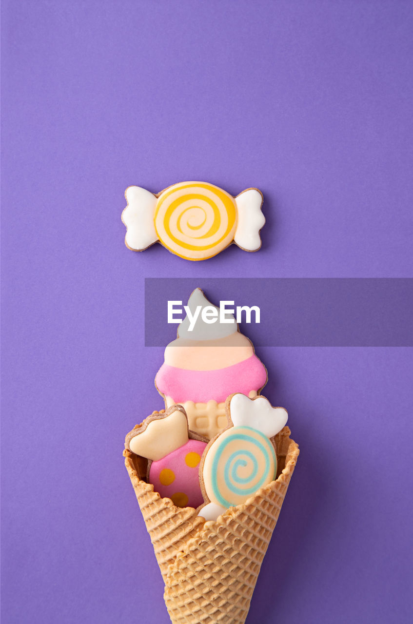 sweet food, sweet, indulgence, indoors, dessert, no people, close-up, food, multi colored, pink color, food and drink, unhealthy eating, candle, flowering plant, still life, freshness, studio shot, flower, colored background, illuminated, temptation, purple