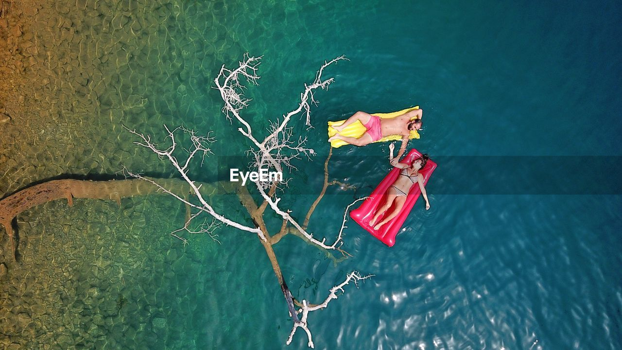 High Angle View Of Couple Relaxing On Inflatable Rafts In Sea