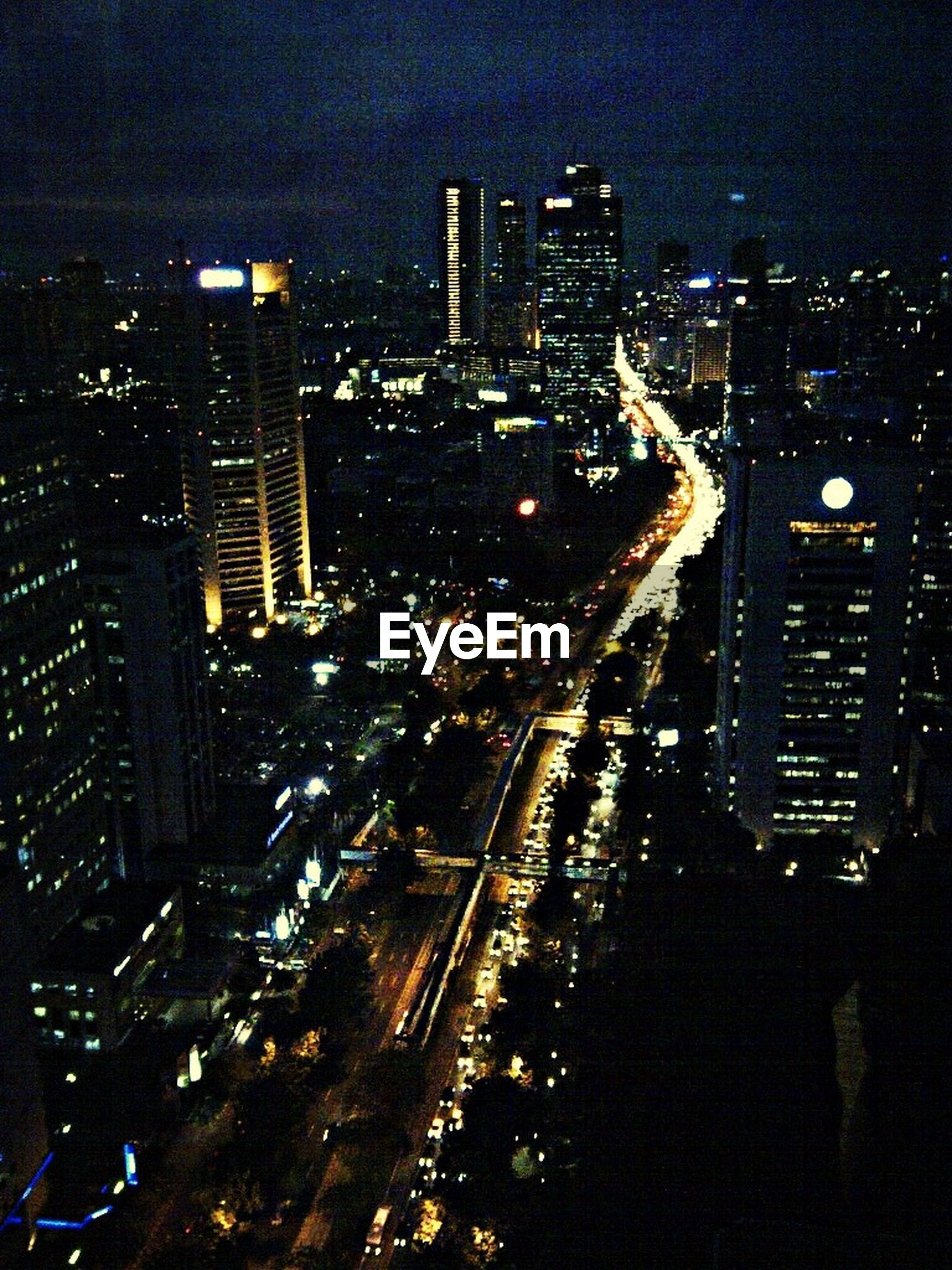 city, illuminated, night, building exterior, architecture, cityscape, transportation, built structure, high angle view, road, city life, street, car, city street, traffic, land vehicle, skyscraper, mode of transport, sky, on the move
