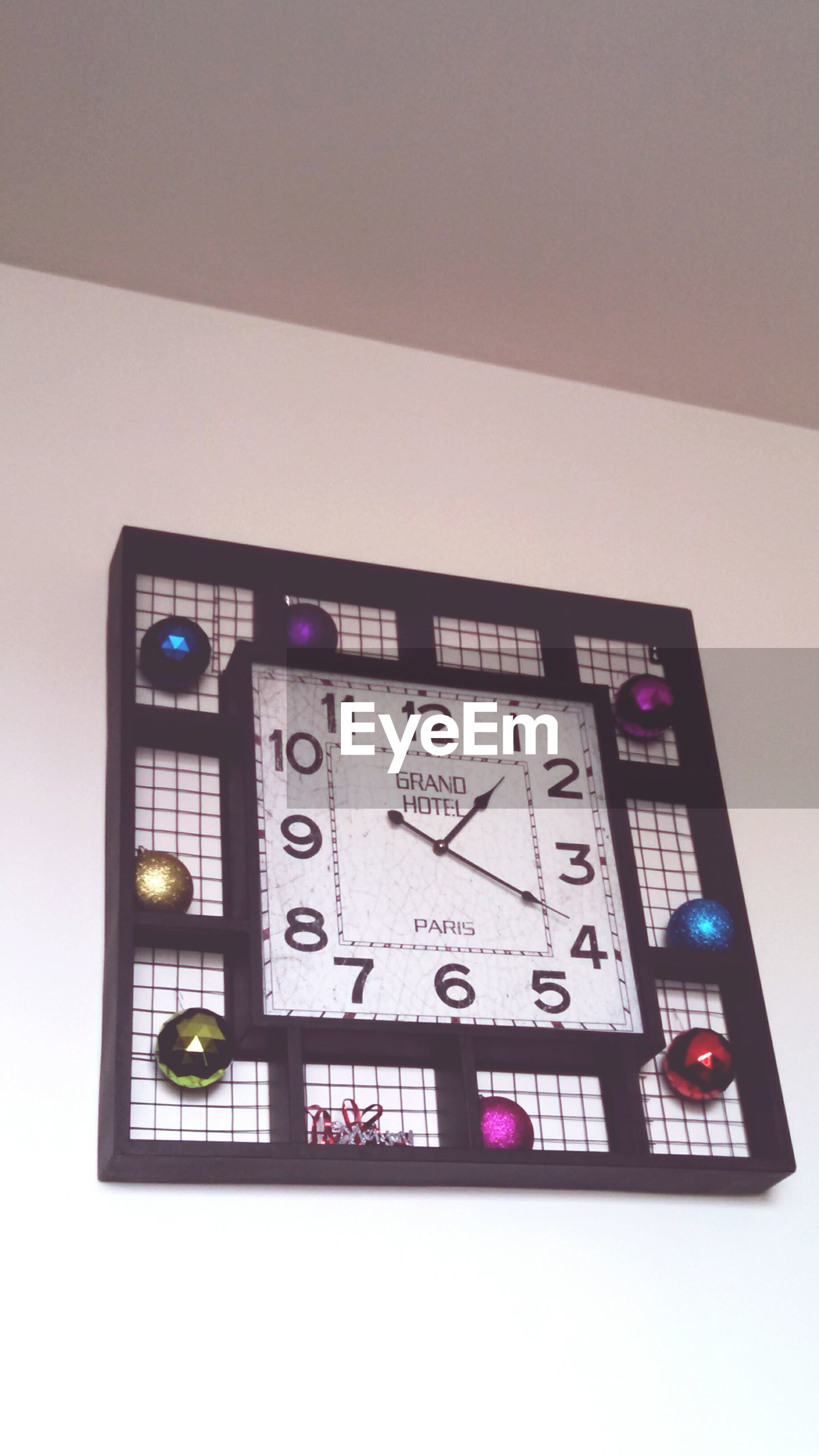 text, communication, western script, indoors, number, capital letter, technology, non-western script, information sign, information, close-up, sign, no people, wall - building feature, low angle view, time, wall, clock, glass - material, picture frame