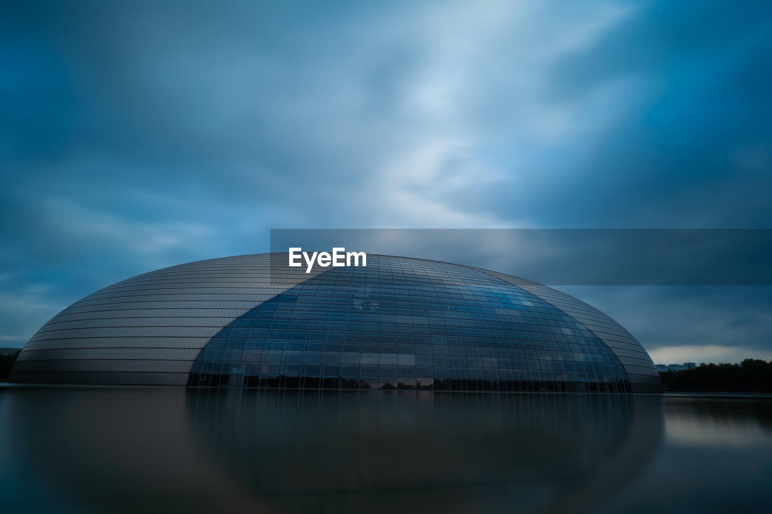 Modern building by lake against overcast sky