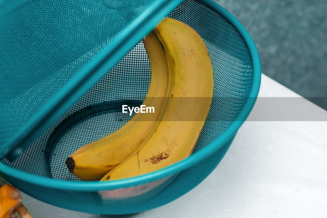 Two yellow bananas in a basket on the kitchen table