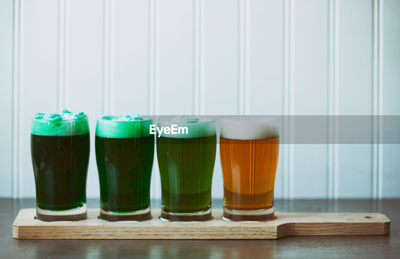 Close-Up Of Beer In Glasses On Table Against Wall