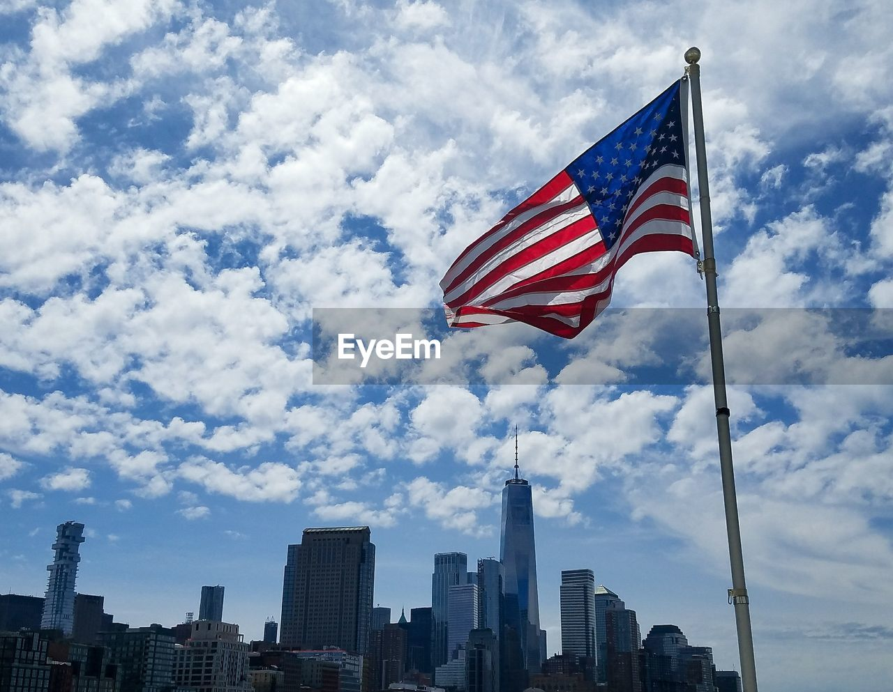 sky, building exterior, cloud - sky, architecture, patriotism, built structure, flag, striped, city, building, nature, low angle view, day, no people, tall - high, landscape, office building exterior, outdoors, wind, cityscape, skyscraper, financial district, independence