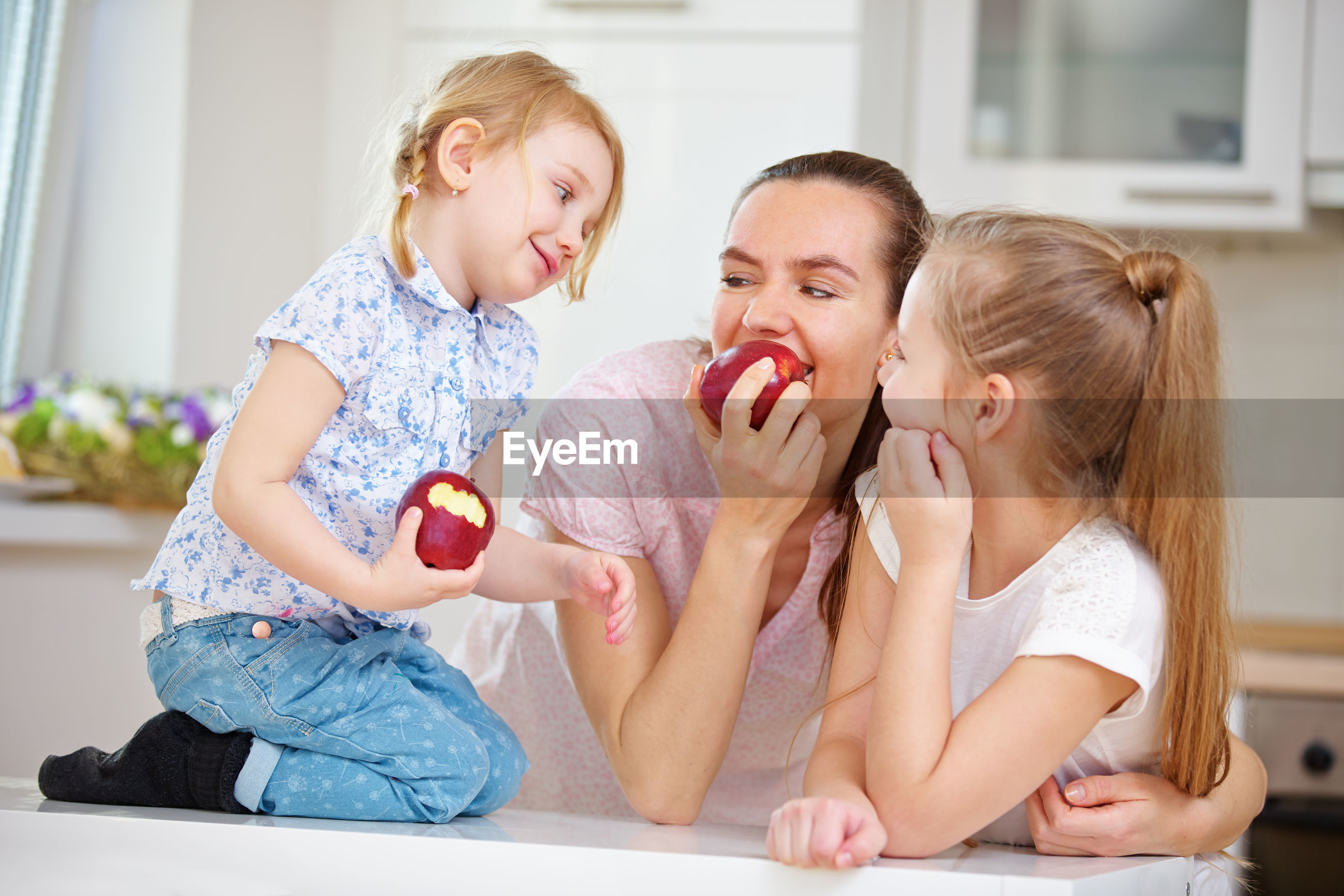 Mother and girls eating apple while sitting at home