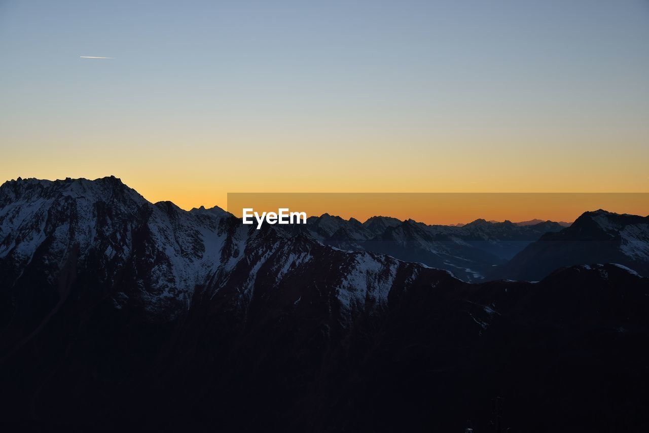 mountain, beauty in nature, sky, scenics - nature, sunset, tranquil scene, tranquility, mountain range, environment, non-urban scene, nature, idyllic, landscape, no people, cold temperature, copy space, clear sky, silhouette, orange color, winter, outdoors, mountain peak, snowcapped mountain