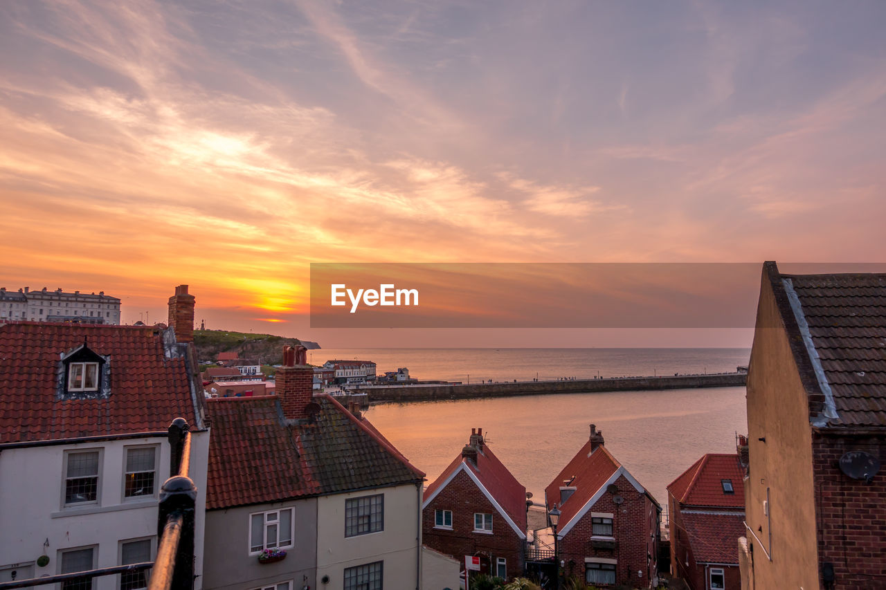 built structure, architecture, sunset, sky, building exterior, building, cloud - sky, city, water, orange color, nature, residential district, no people, house, roof, scenics - nature, outdoors, horizon, high angle view, row house