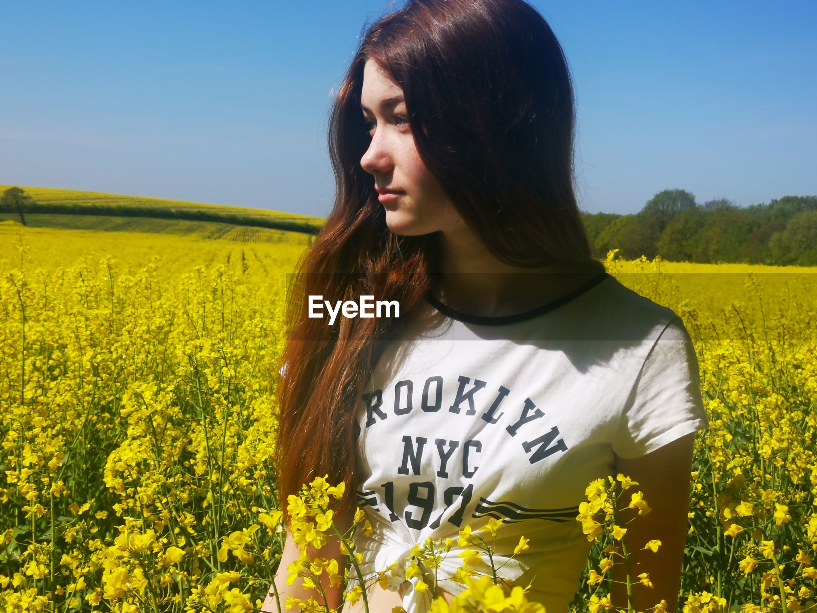 YOUNG WOMAN STANDING BY YELLOW FLOWER FIELD