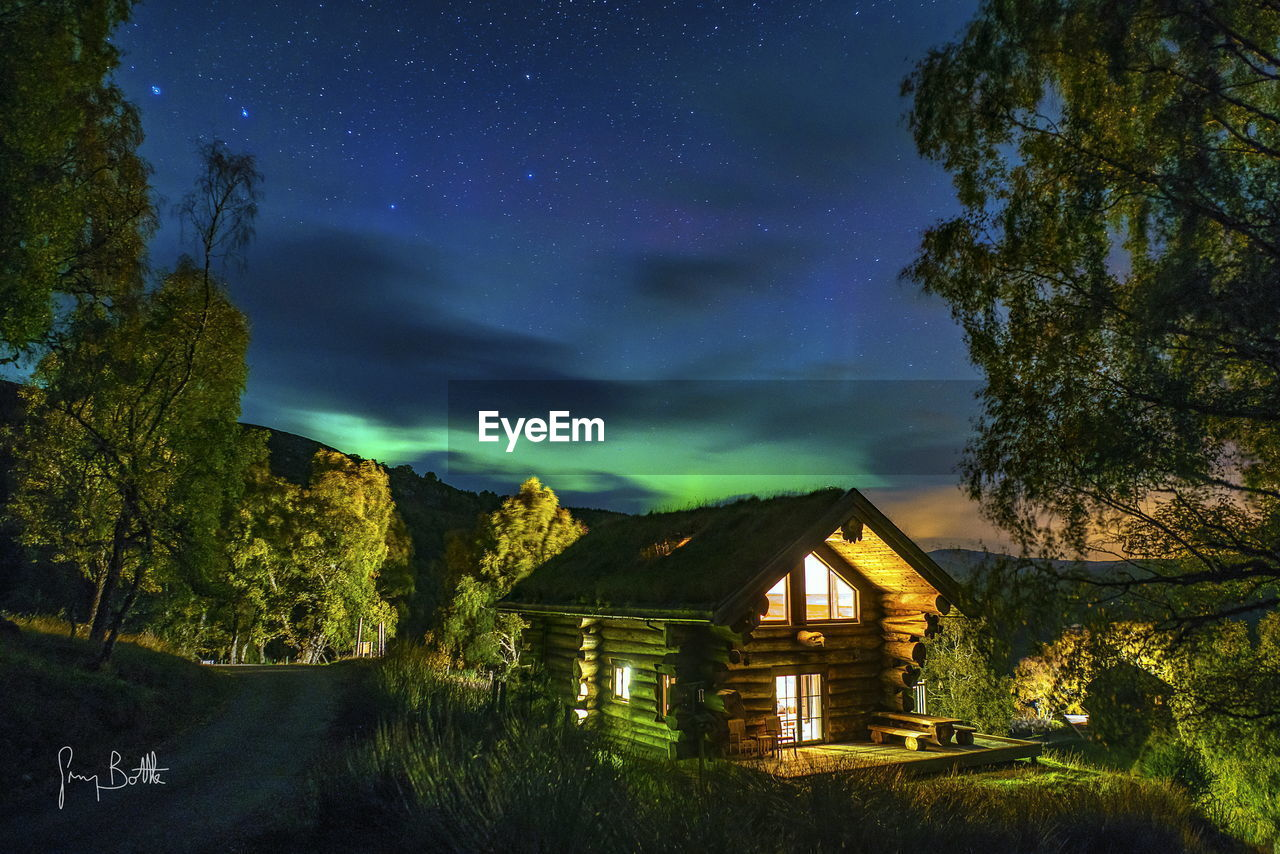 tree, tranquility, sky, tranquil scene, night, scenics, nature, beauty in nature, no people, house, architecture, built structure, outdoors, illuminated, star - space, building exterior, grass, astronomy, galaxy