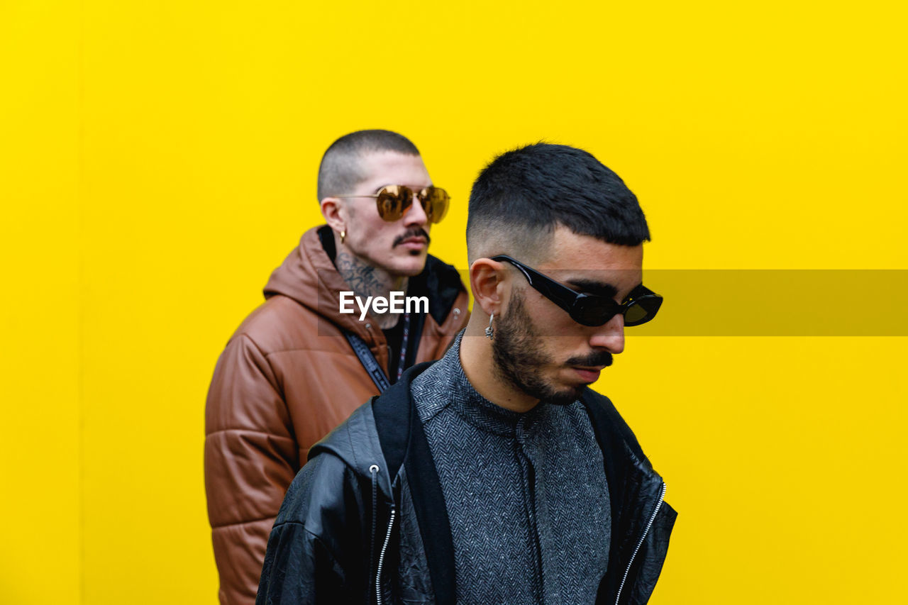 yellow, glasses, sunglasses, fashion, young men, young adult, lifestyles, studio shot, colored background, waist up, casual clothing, yellow background, indoors, people, front view, real people, two people, facial hair, standing, men