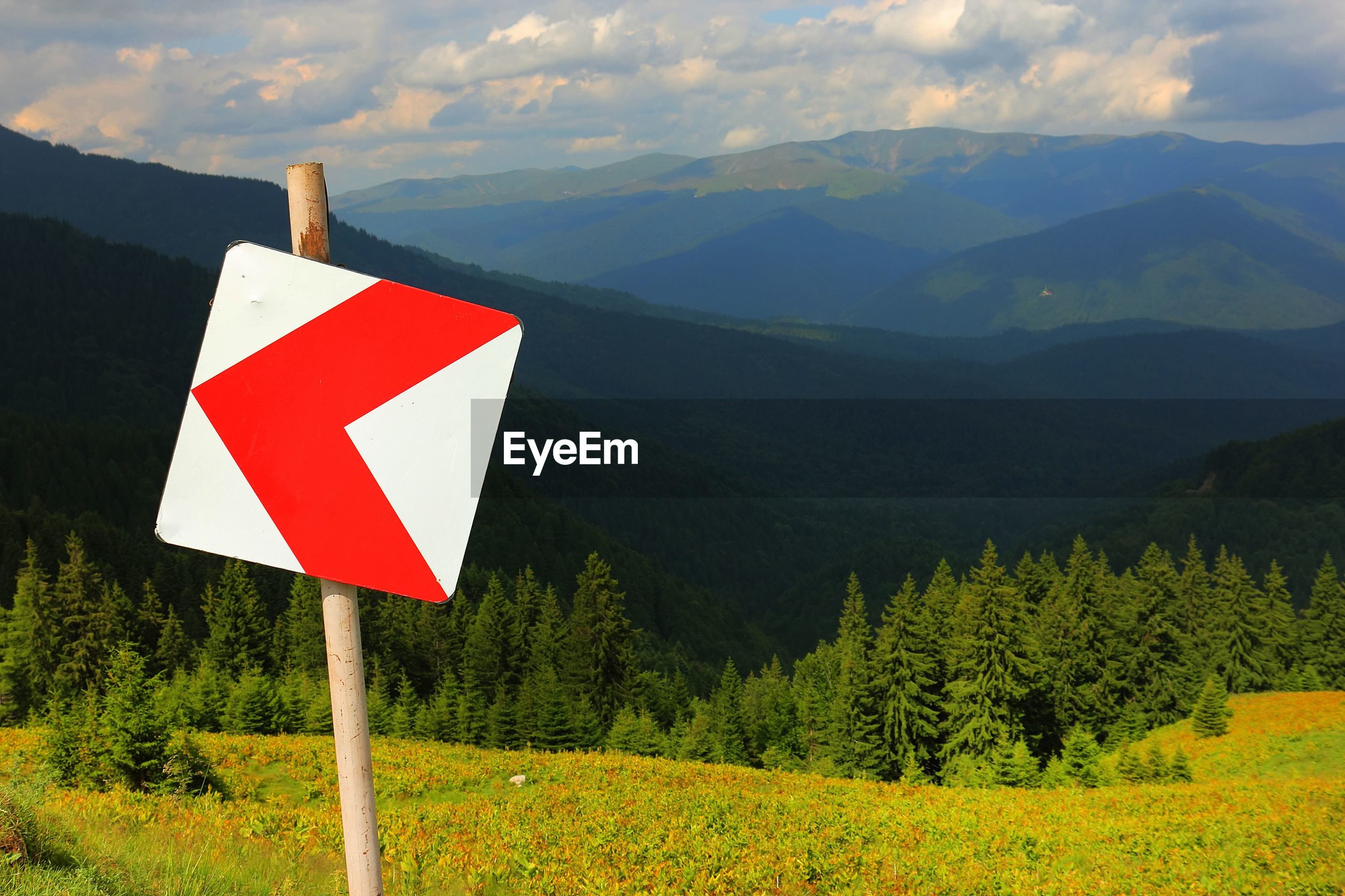 Directional sign on field against carpathians mountains
