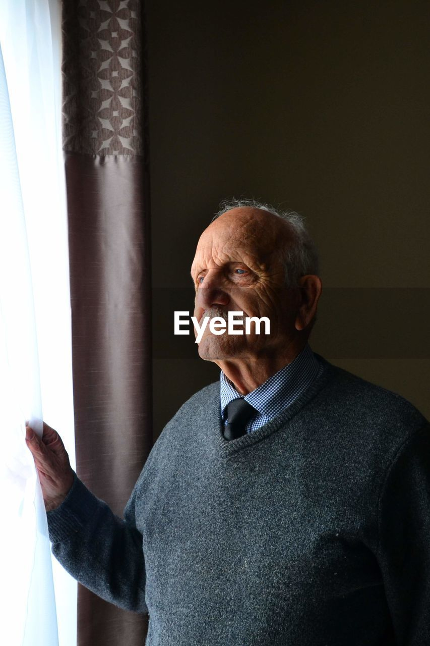 Senior Man Standing By Window At Home