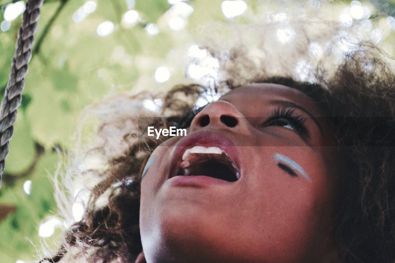 Close-up of girl with mouth open looking up against tree