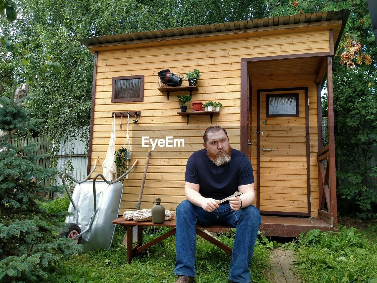 FULL LENGTH OF MAN SITTING OUTSIDE HOUSE