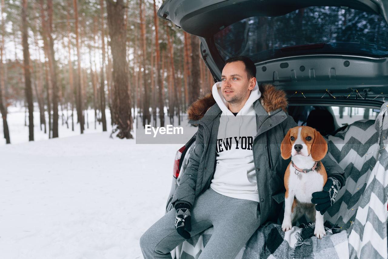 Man with dog sitting in car trunk