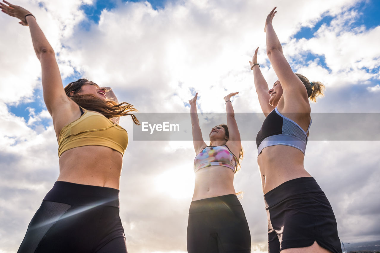 Low angle view of women jumping against sky