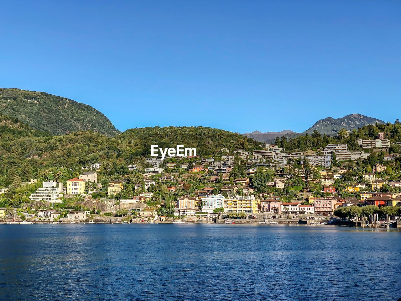 Scenic View Of Townscape By Sea Against Clear Blue Sky