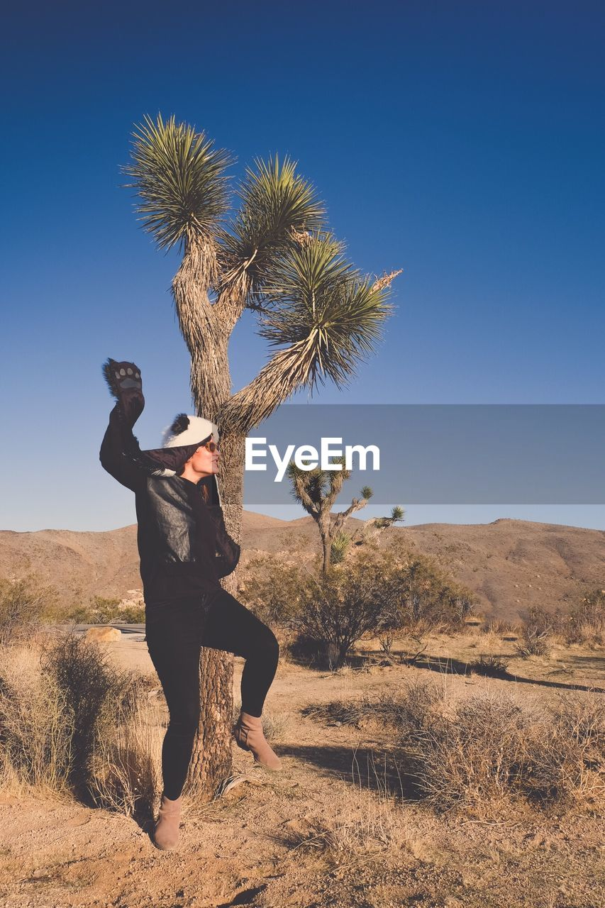 sky, plant, land, lifestyles, one person, real people, full length, nature, beauty in nature, leisure activity, landscape, environment, sunlight, day, field, tree, scenics - nature, casual clothing, young adult, desert, outdoors, human arm, climate, arms raised