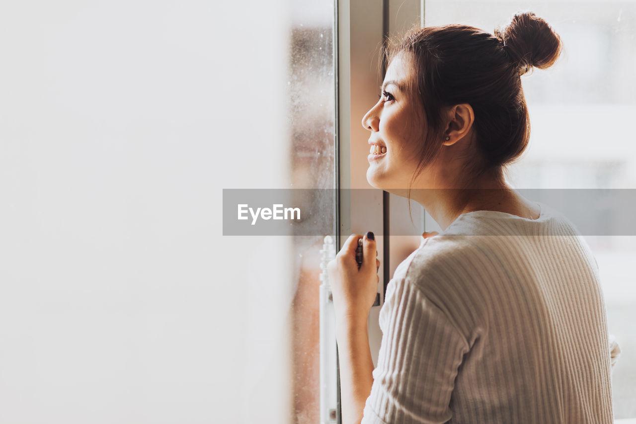 Woman looking away through glass window