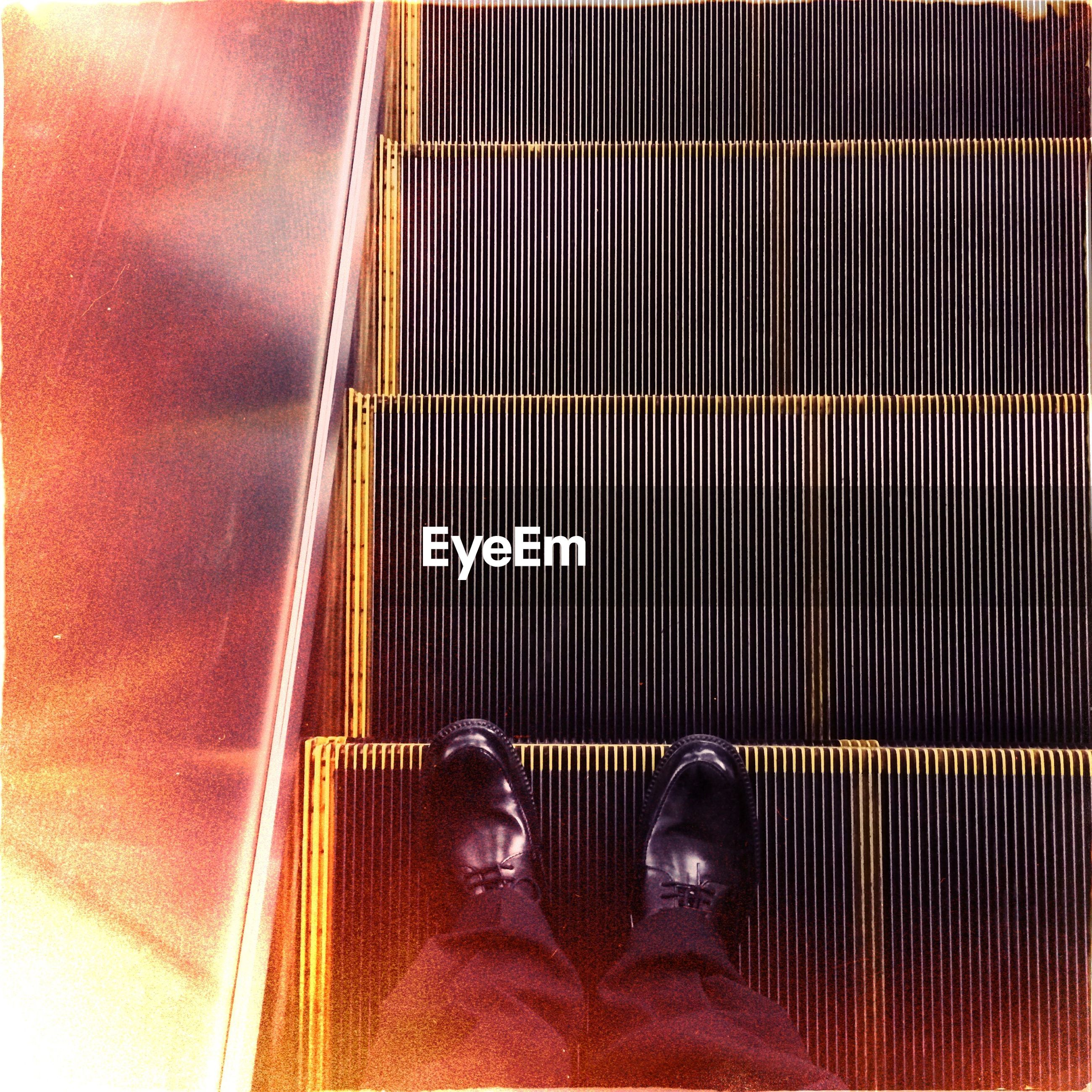 Low section view of man on escalator