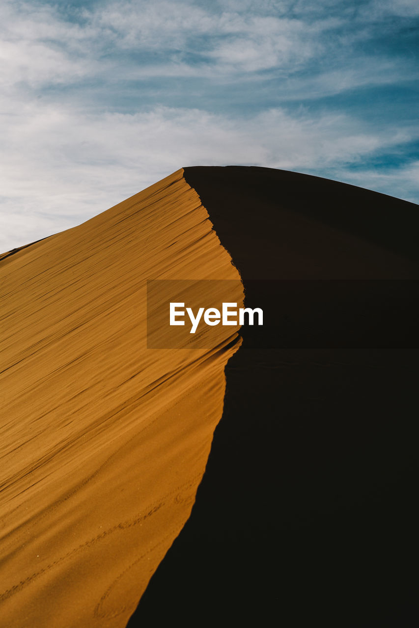 Low Angle View Of Sand Dune At Desert Against Sky