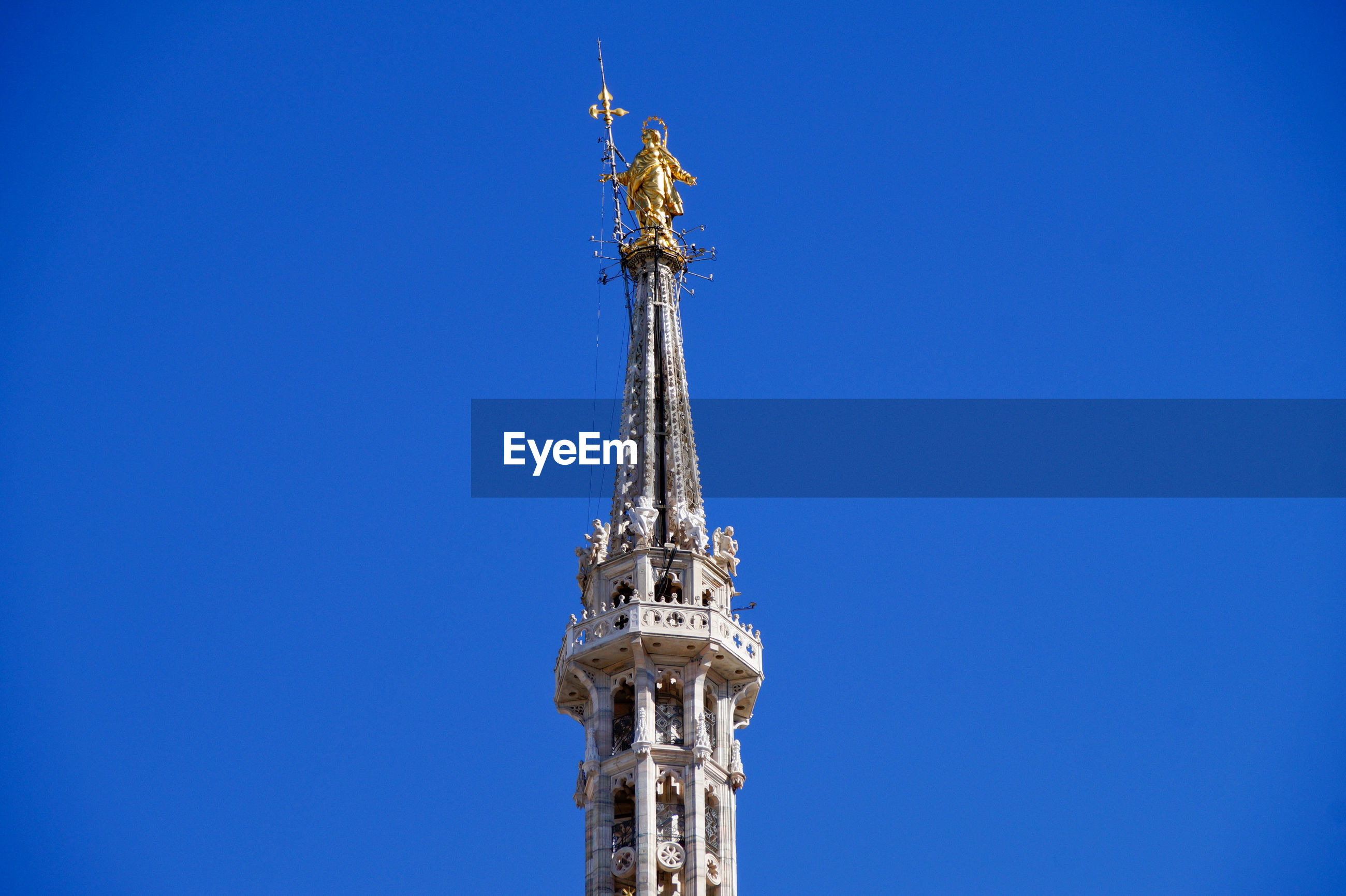 Low angle view of statue at duomo di milano against clear blue sky