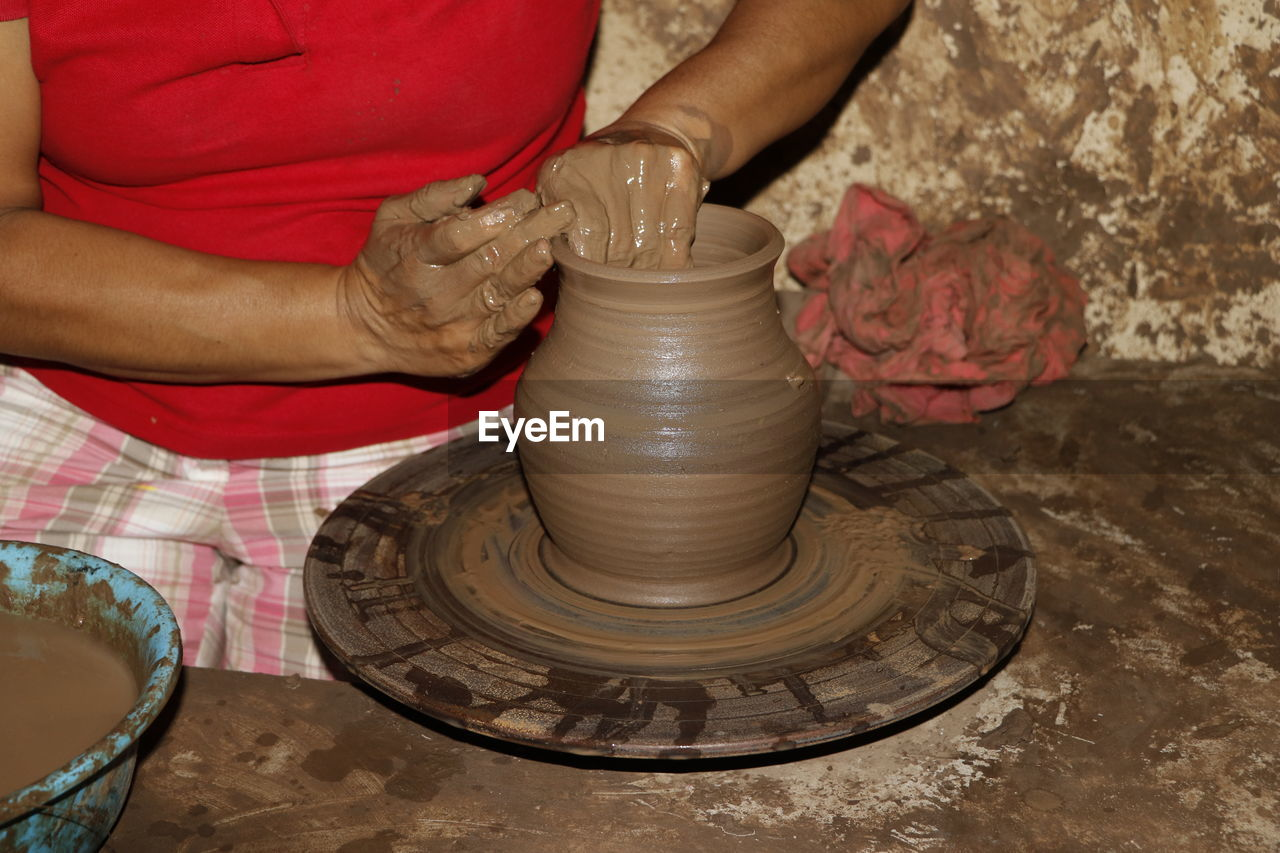pottery, craft, art and craft, making, human hand, clay, skill, one person, hand, real people, molding a shape, spinning, occupation, creativity, working, expertise, human body part, holding, midsection, indoors, preparation, mud