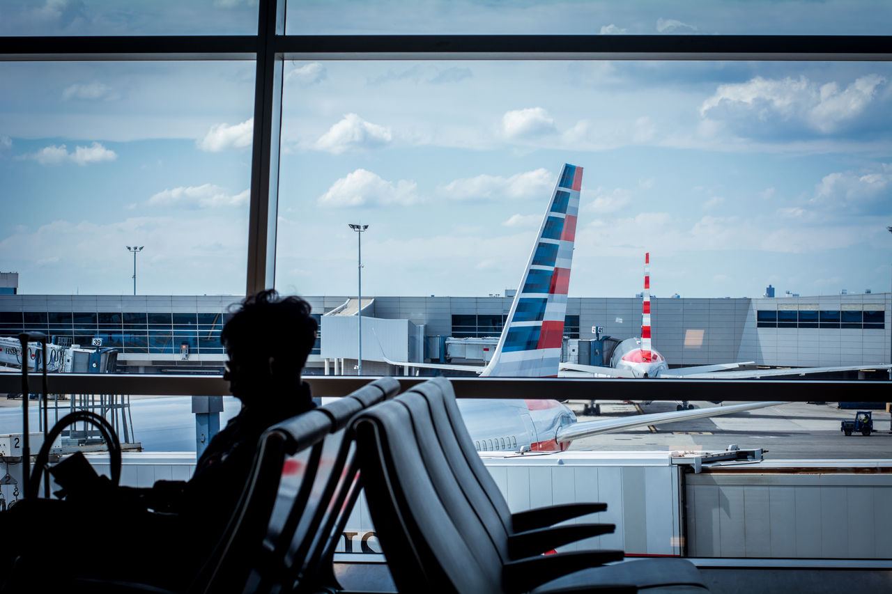 REAR VIEW OF WOMAN SITTING ON AIRPORT AGAINST SKY