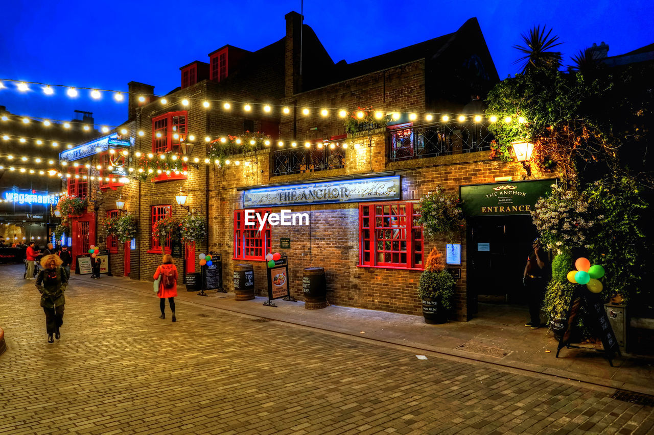 illuminated, night, architecture, building exterior, real people, store, built structure, men, outdoors, christmas, lifestyles, nightlife, christmas decoration, women, tree, neon, city, sky, people