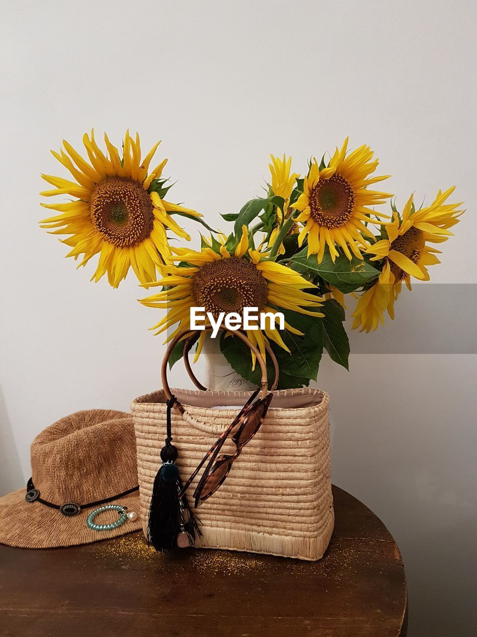 flower, flowering plant, yellow, freshness, plant, table, still life, indoors, beauty in nature, flower head, vase, vulnerability, no people, sunflower, petal, nature, fragility, close-up, inflorescence, container, flower arrangement, bunch of flowers