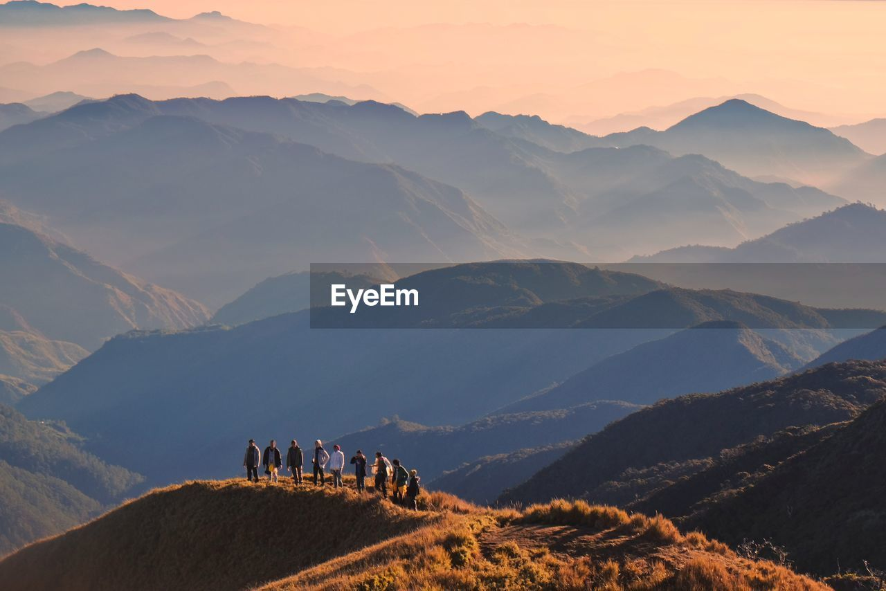 High angle view of people standing on hill against mountain range