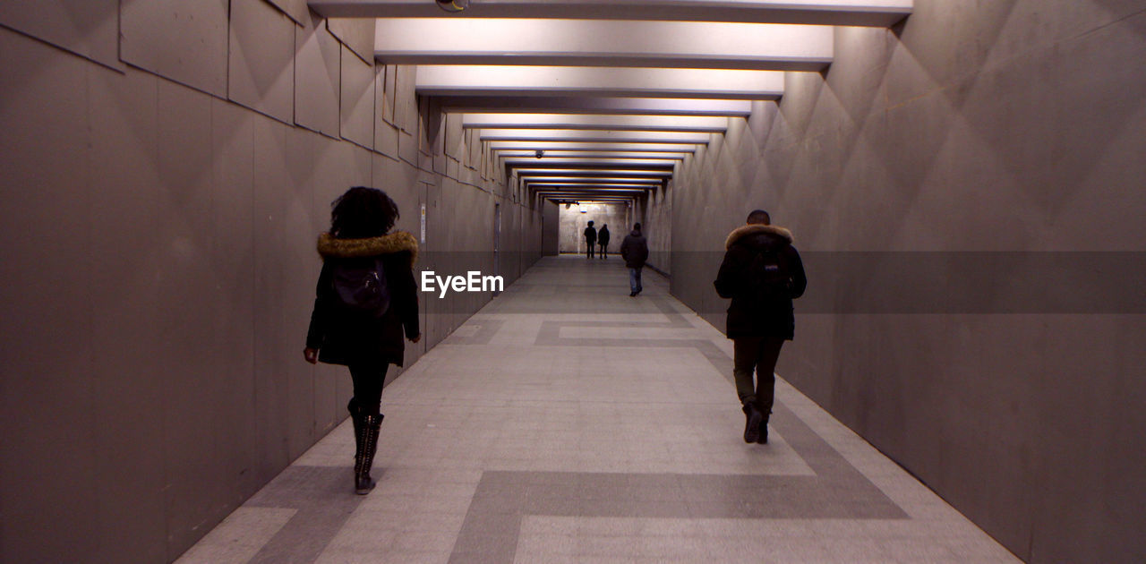 FULL LENGTH REAR VIEW OF PEOPLE WALKING IN SUBWAY