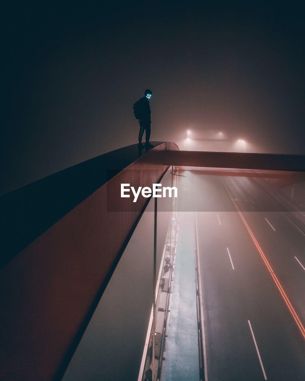 SILHOUETTE MAN ON ILLUMINATED ROAD AT NIGHT
