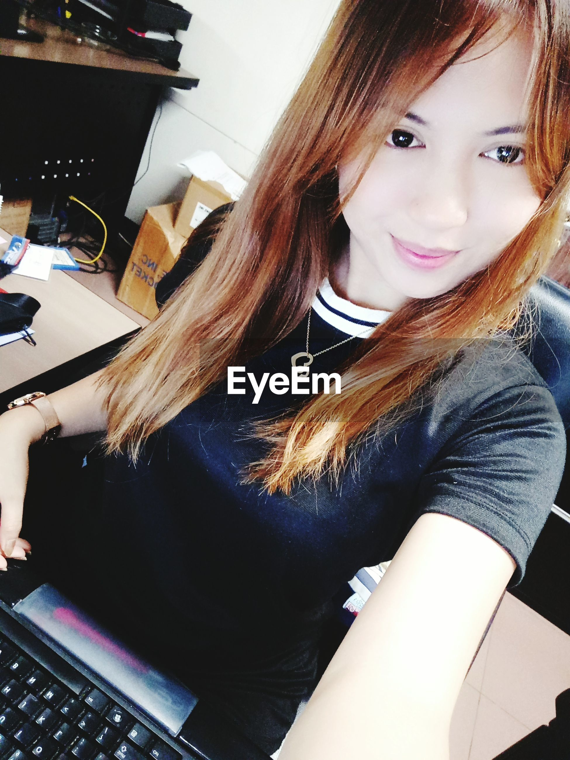 technology, looking at camera, indoors, real people, one person, sitting, smiling, young adult, portrait, young women, long hair, high angle view, wireless technology, casual clothing, medium-length hair, computer, communication, desk, happiness, keyboard, day, using laptop