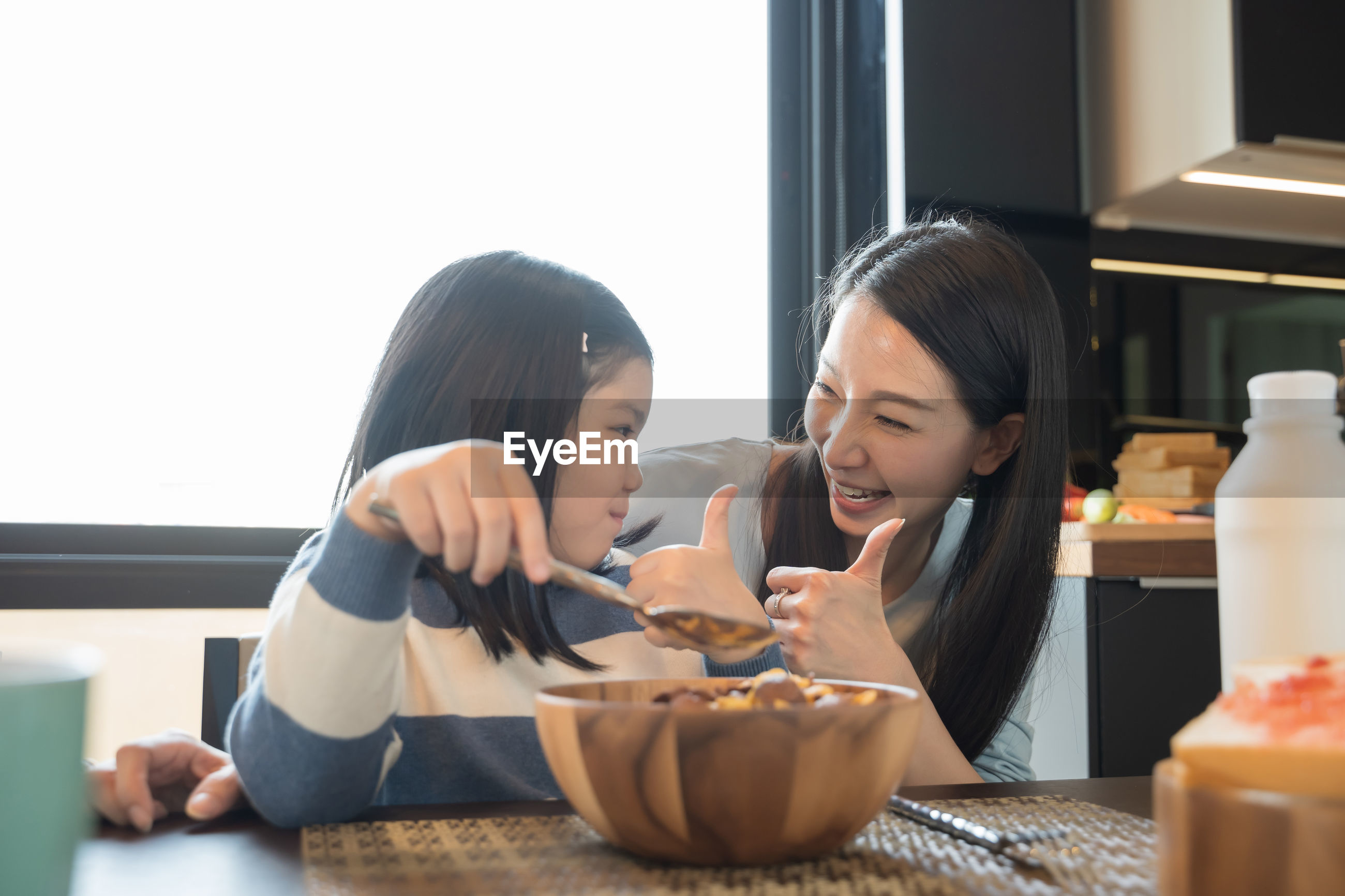 Girl and woman gesturing with breakfast on table