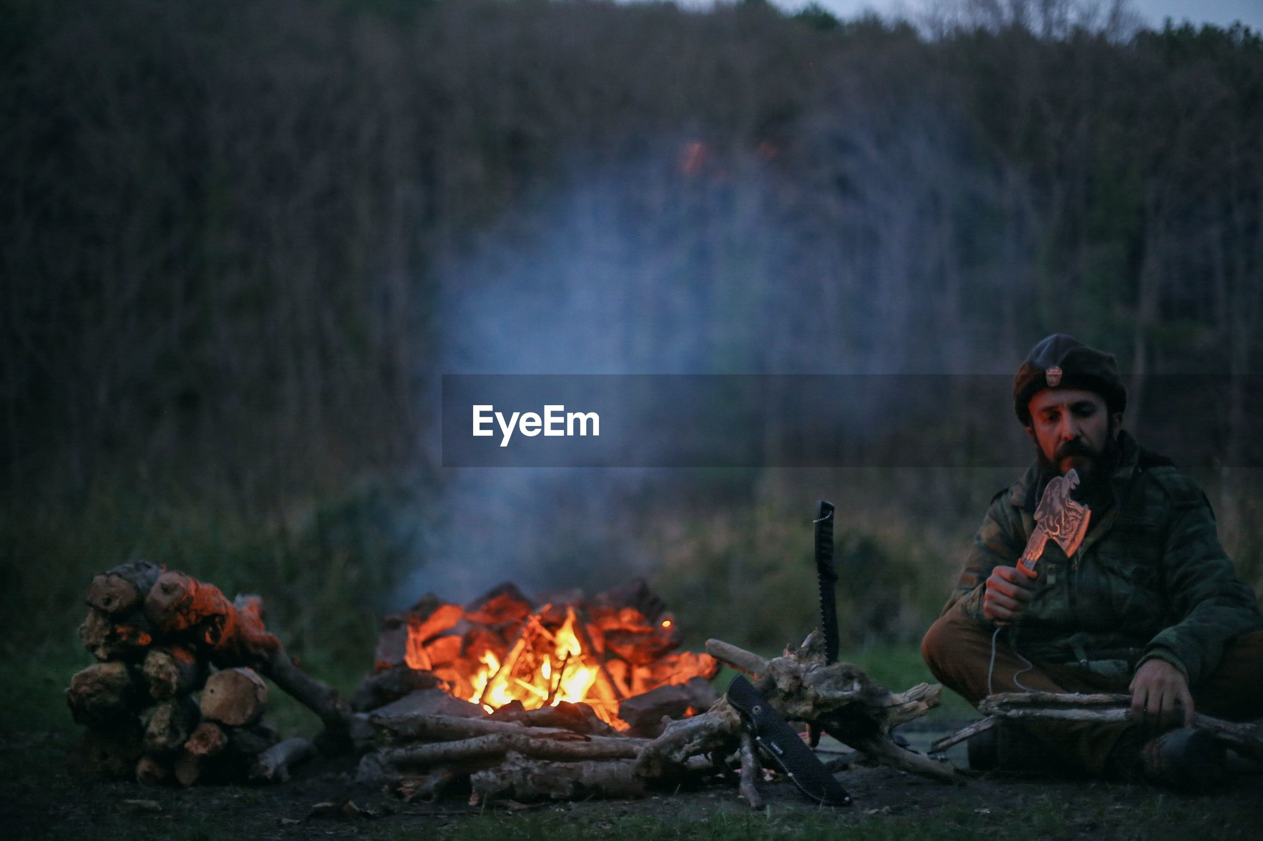 Mid adult man cutting wood by campfire on field at dusk