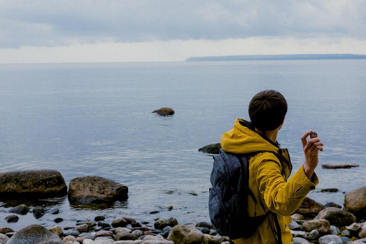Side View Of Man Throwing Stones In Sea Against Sky