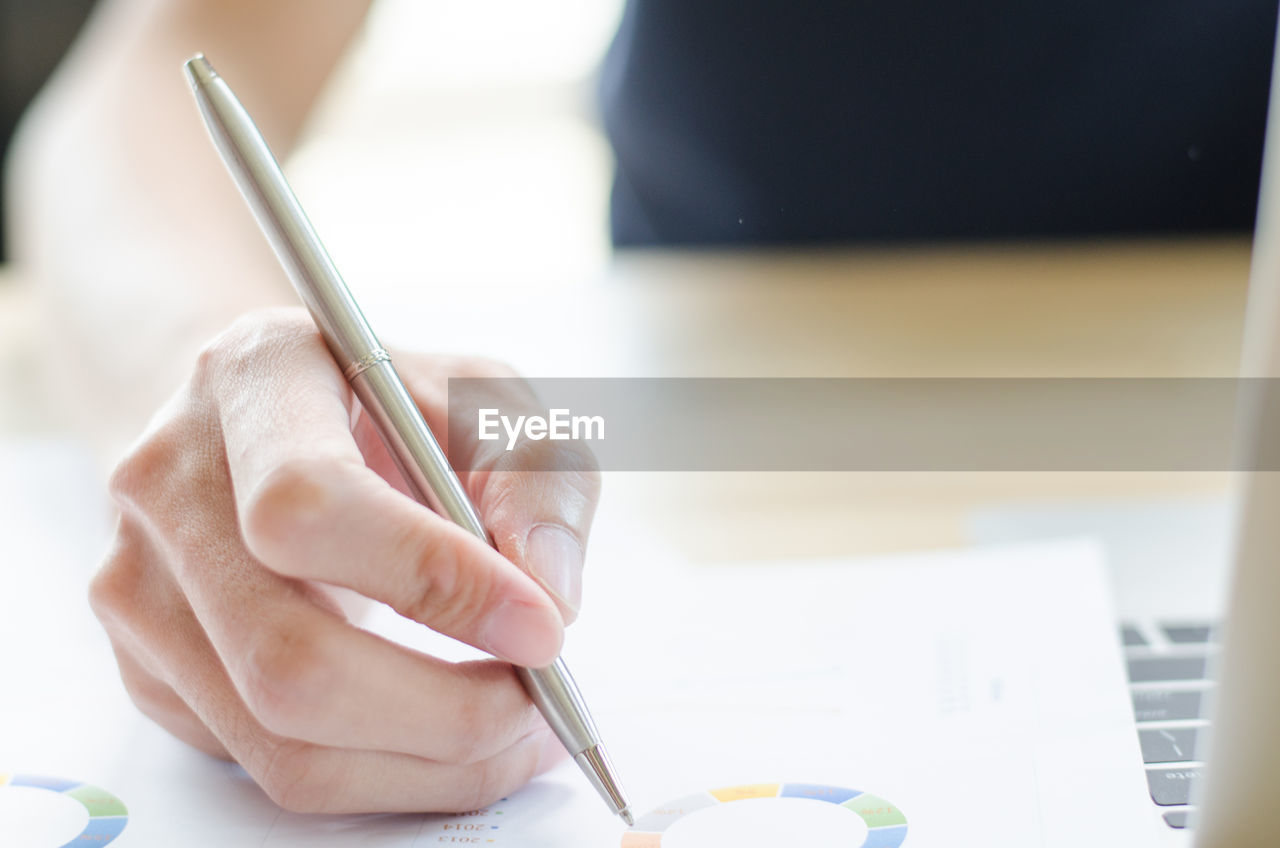 Cropped Hand Of Businesswoman Writing On Document At Desk