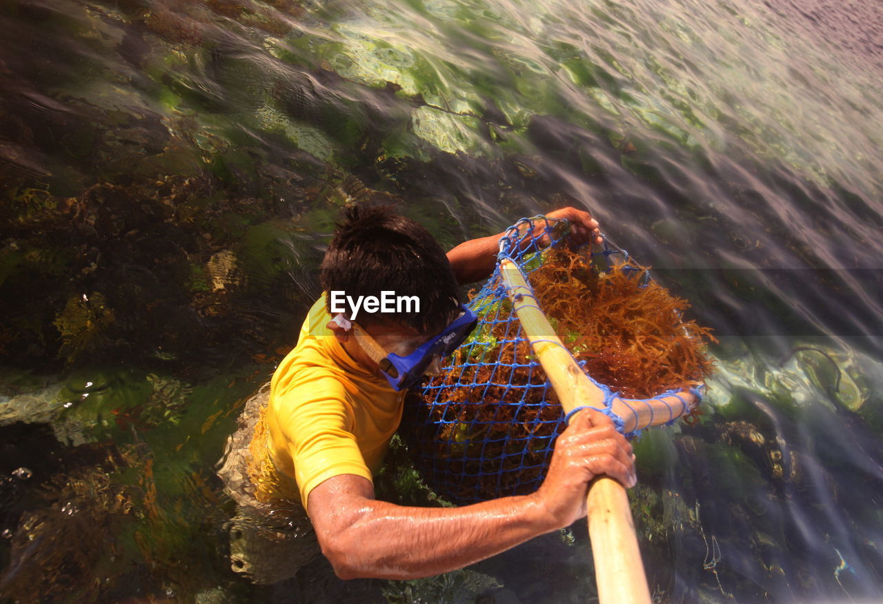 Man holding fishing net with coral in sea