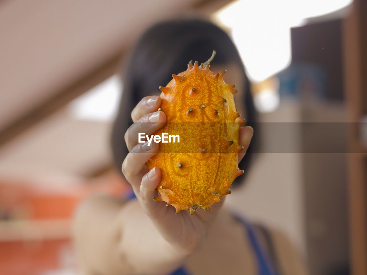Close-Up Of Woman Showing Horned Melon