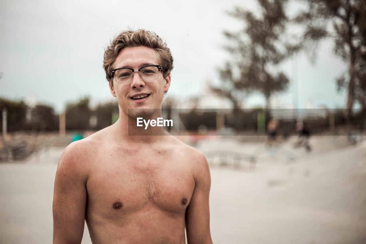 Portrait Of Smiling Shirtless Man Standing At Skate Park