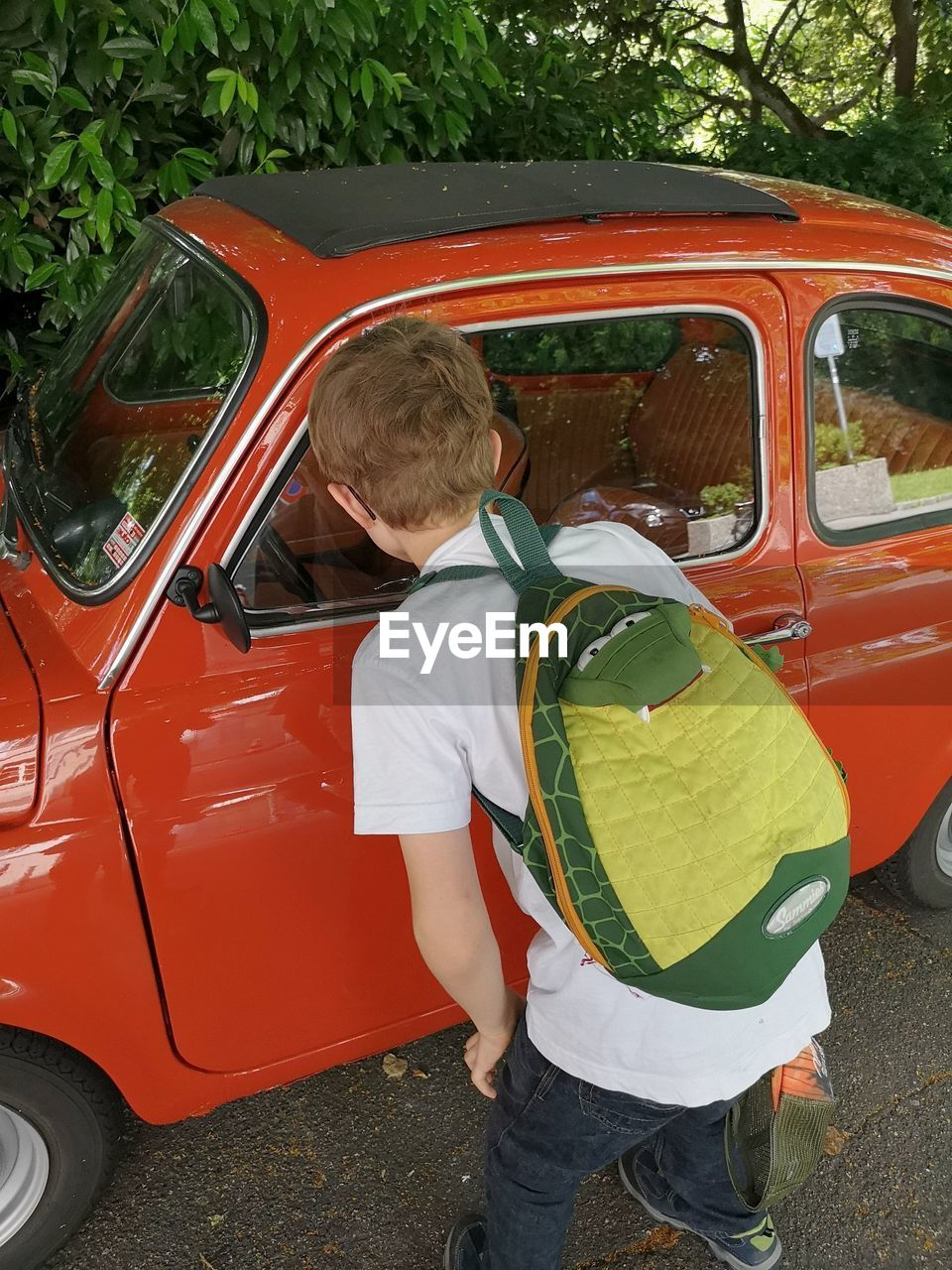 mode of transportation, transportation, real people, childhood, boys, one person, day, three quarter length, men, males, child, land vehicle, car, leisure activity, motor vehicle, red, casual clothing, lifestyles, outdoors, shorts