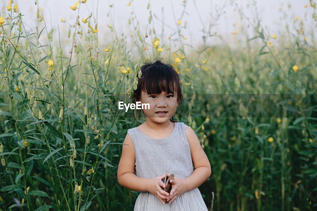 child, childhood, one person, real people, plant, growth, field, standing, land, leisure activity, casual clothing, front view, lifestyles, looking at camera, portrait, nature, innocence, day, outdoors, bangs, hairstyle